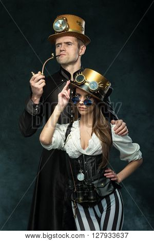 The couple steampunk. A man with a pipe and a girl with glasses and hat.