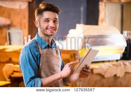 Like what you do. Cheerful handsome young smiling waiter using tablet and expressing gladness while working in the cafe
