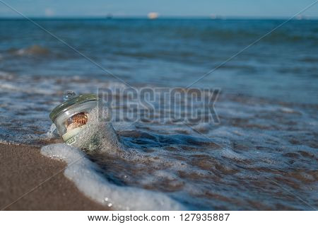 in the sand in the surf is the glass jar with money and shells gift sea