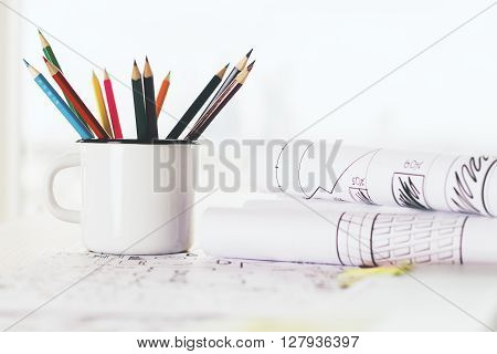 Iron mug with pencils on tabletop with sketches on rolled paper sheets