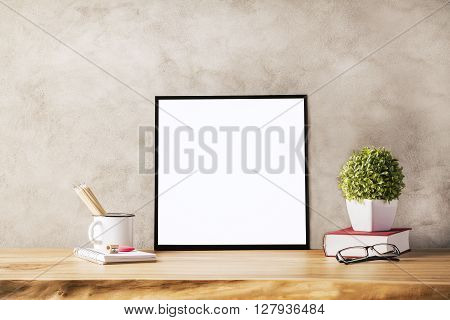 Closeup of wooden table with blank frame flowerpot iron mug with pencils and glasses on concrete background. Mock up