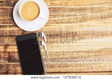 Topview of coffee cup and black phone with headphones on wooden table. Mock up