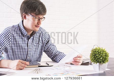 Young caucasian man sitting at office desk with business sketch and plant and looking at paper sheet