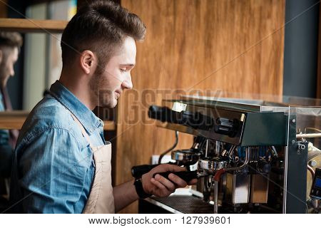Like doing it. Pleasant delighted positive barista using coffee machine and making beverage while  feeling glad