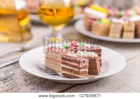 Assorted different mini cakes with cream, studio shot