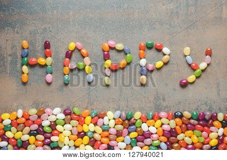 Word happy written with jelly beans dark background with colorful border