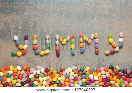 Word yummy written with jelly beans dark background with colorful border