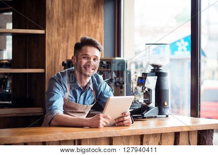 Ready to work for my guests. Pleasant smiling delighted handsome barista standing at the counter and expressing gladness while using tablet