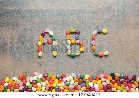 Word abc written with jelly beans dark background with colorful border