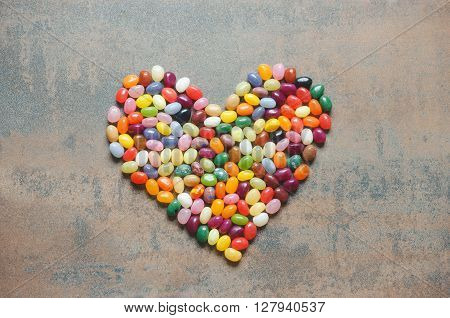 Heart symbol from jelly beans on dark background love concept