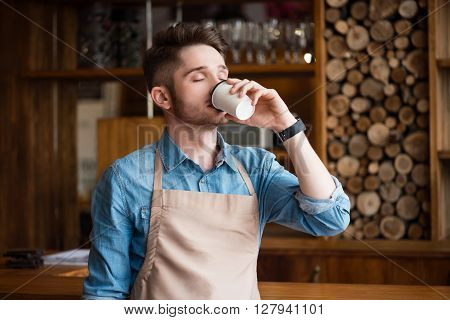 Enjoy the taste. Pleasant content handsome waiter drinking coffee and feeling glad while standing in the cafe