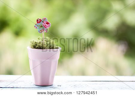 paper flower in a pot on a green background