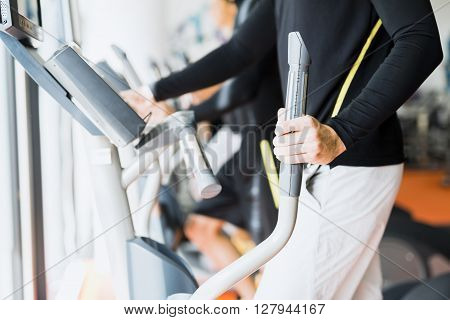 Young healthy group of people working out on a elliptic trainer in a fitness center