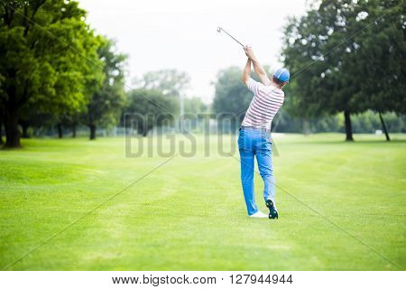 Golfer practicing and concentrating before and after shot during a nice sunny day