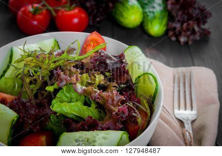 Fresh vegetable salad, healthy food, organic cucumbers, tomatoes and salad leaves