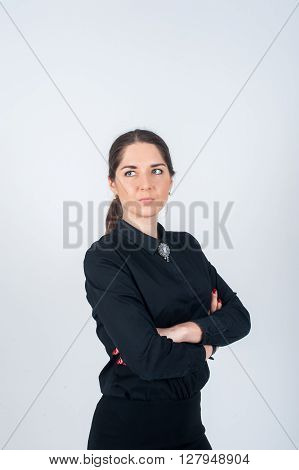 Business woman standing sideways simply in black shirt hands folded on his chest