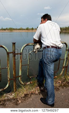 Pripyat, Ukraine - May 9, 2011: Man, holding gas mask, leans on fence in front of river in his hometown in Chernobyl Exclusion Zone, place of Chernobyl nuclear disaster. Every year on May 9 evacuated people are allowed to visit their former homes.