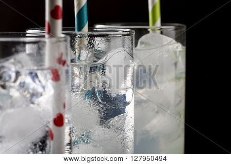 Set from three a collins glass with cocktails and colored straws. Decorated melted ice cubes.