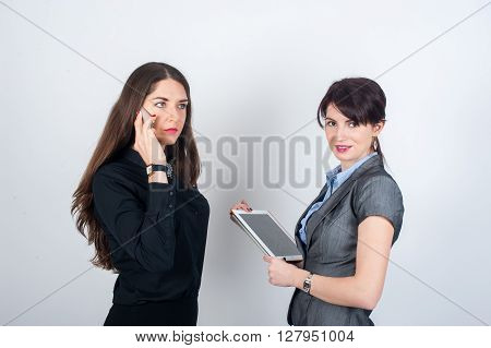 Two business women standing on a light background one talking on the phone and the other works on the tablet