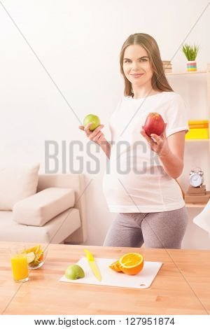 I prefer healthy food. Cheerful young expectant mother is holding apples. She is standing and smiling. The lady is looking at camera with happiness