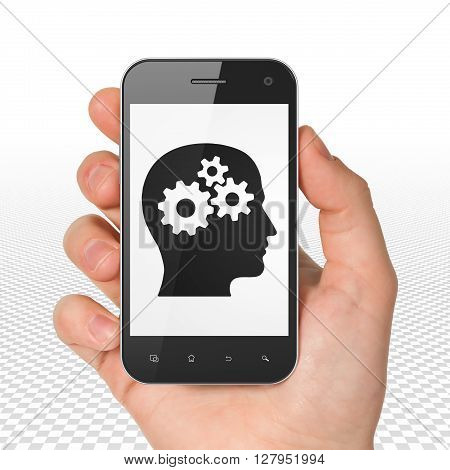 Business concept: Hand Holding Smartphone with  black Head With Gears icon on display,  Tag Cloud background, 3D rendering