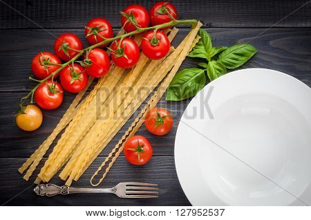 Italian spaghetti, served plate, on a wooden table with bunch tomatoes. Top view.