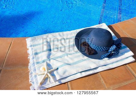 towel and summer blue hat  near pool at sunny summer day