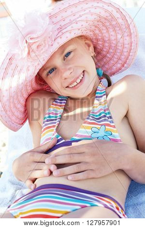 Happy cute child lying down on deckchair of beach resort for summer holidays or travel vacations