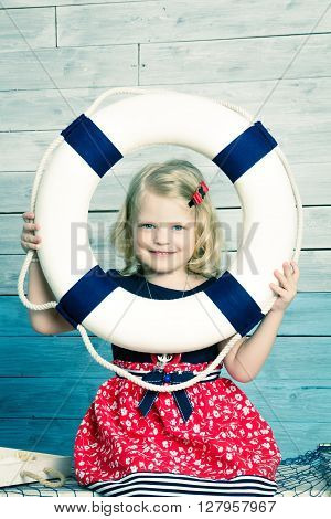 little girl holding a lifebuoy and laughing looking at camera