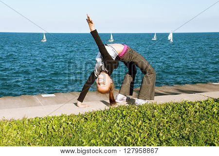 Girl doing gymnastics on the shores of Lake Michigan