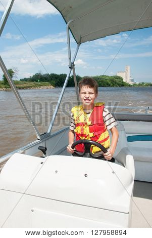 Boy operate the boat on the Illinois River, USA