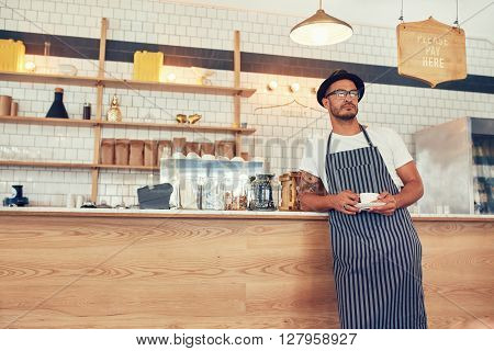 Cafe Owner Standing At Counter With A Cup Of Coffee