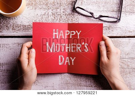 Hands of unrecognizable woman holding Mothers Day greeting card. Cup of tea and eyeglasses. Studio shot on wooden background.