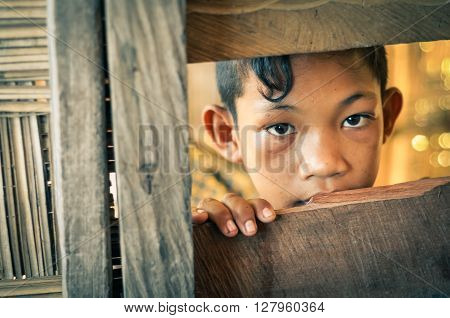 Malange Indonesia - June 2015: Young native boy with nice dark brown eyes looks to photocamera from hole in wooden wall in Malange Togean islands Sulawesi Indonesia. Documentary editorial.