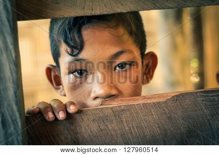 Malange Indonesia - June 2015: Young boy with curl of black hair and nice brown eyes looks to photocamera through hole in wooden wall in Malange Togean Islands Sulawesi Indonesia. Documentary editorial.
