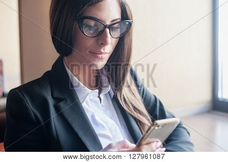 Girl in a suit with glasses and carefully reads something in the phone