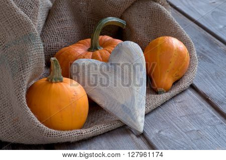 Wooden heart with copy space and pumpkins on weathered boards