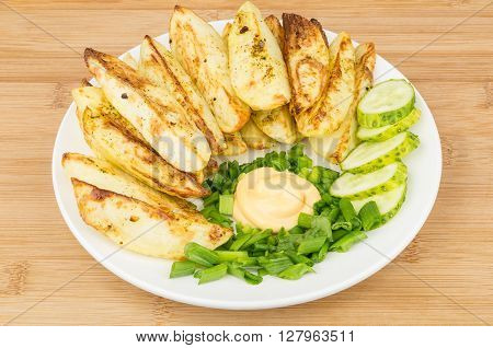 Plate of slices of baked potatoes with mayonnaise and leek on wooden table