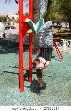 Girl in a sports simulator training on the playground outdoors