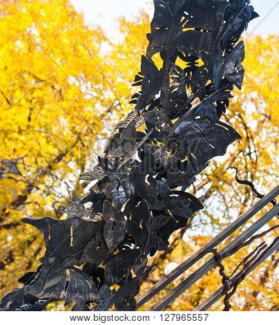 Beautiful butterfly on a big metal arch in autumn park.