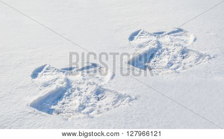 Two figures in the snow angel on snow background