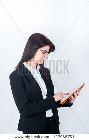 Woman in suit holding a tablet and runs her finger across the screen