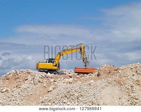 excavator loading tipper truck on construction site