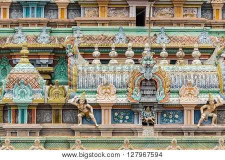 Trichy India - October 15 2013: Closeup of a statue scenery at Ranganathar Temple showing Lord Vishnu in his Narasimha avatar killing the demon Hiranyakashipu. Detail on Gopuram.