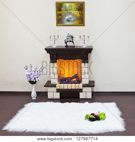 Interior of living room with a fireplace and white fur carpet. The fire in the fireplace.