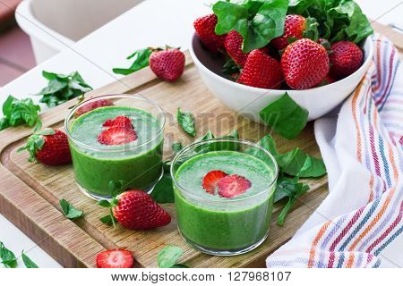 Healthy green smoothie in a glass with strawberry on a wooden cutting board. Outdoor summer background, selective focus