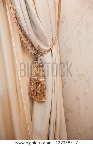 Part of beautifully draped curtain with tassels