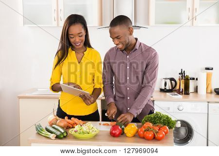 Young African American Couple In Home Kitchen Using Electronic Tablet