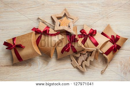 Handmade Christmas gifts from kraft paper and wooden toys on the Christmas tree.