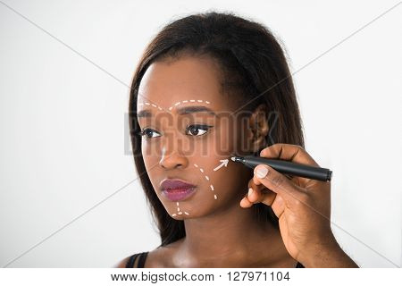Close-up Of Person's Hand Drawing Correction Line On Young African Woman's Face